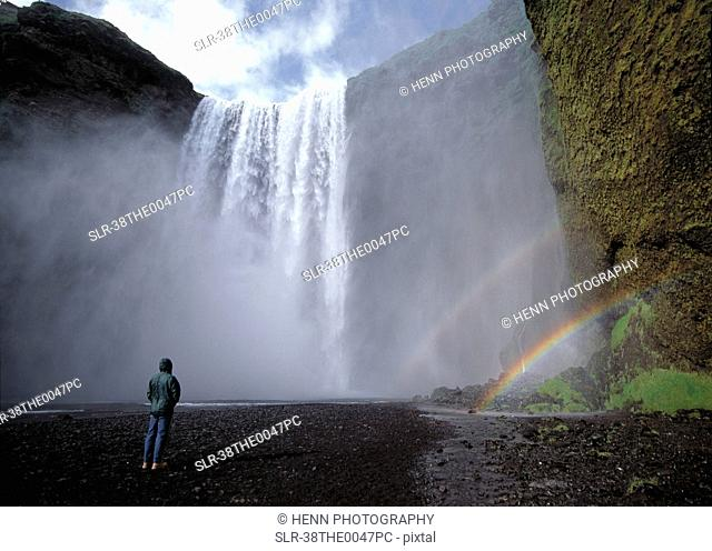 Hiker admiring rainbows in waterfall