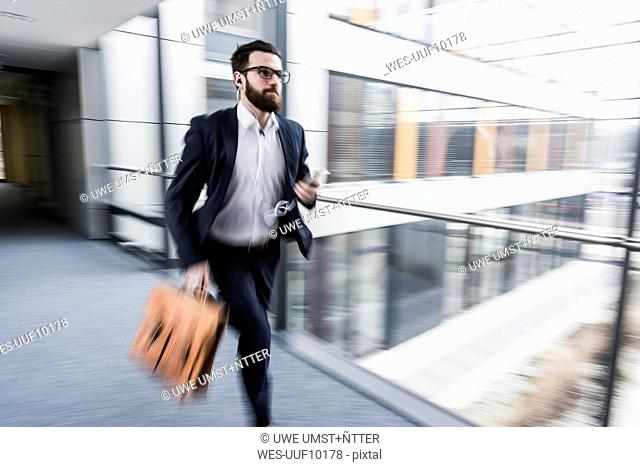 Businessman running in corridor of an office building