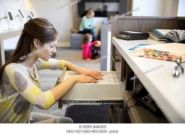 Receptionist looking through drawer in dentists office