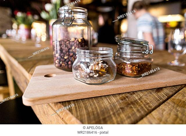 Close-up of nuts and chili flakes in jar on restaurant table