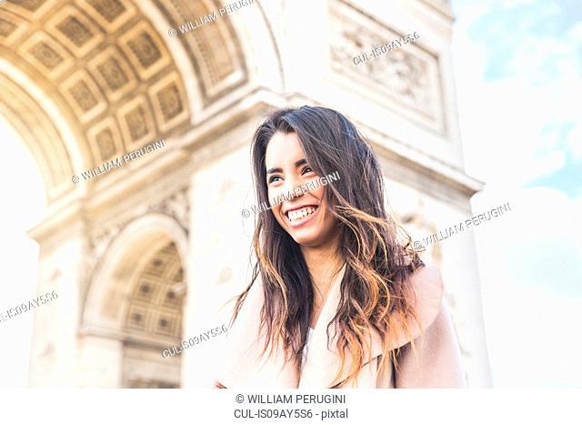 Happy young woman in front of Arc de Triomphe, Paris, France
