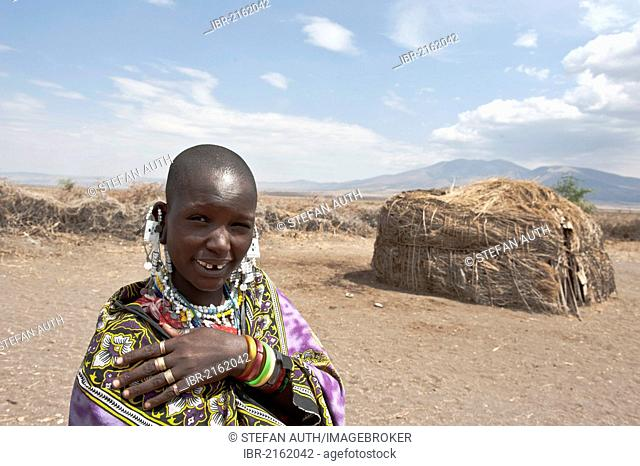 Portrait, ethnology, Maasai woman wearing jewellery, Maasai, in front of Hut made of Straw and branches, village of Kiloki, savannah