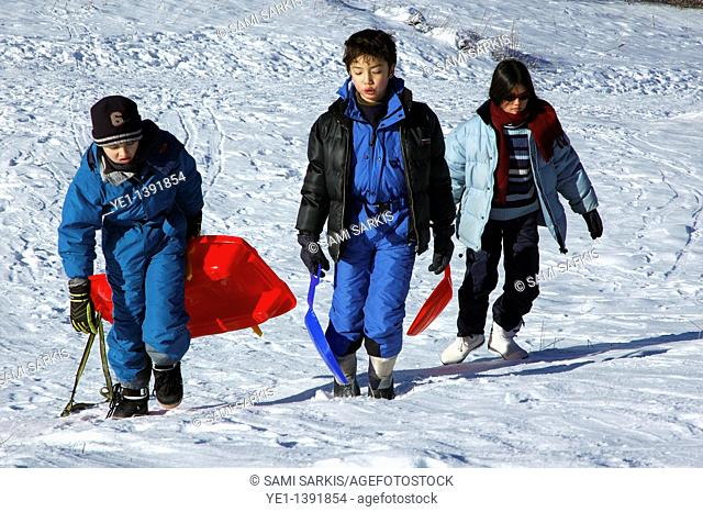 Three children carrying sleds up a snowy hill
