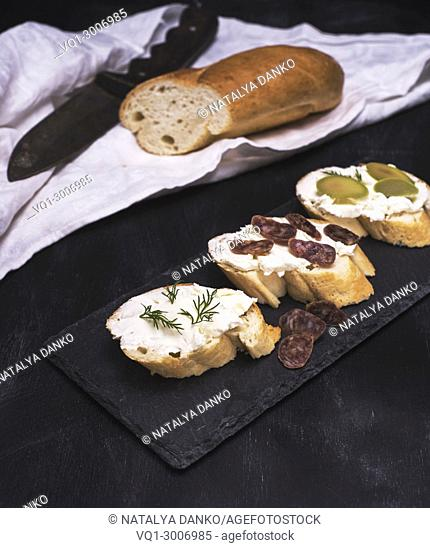 sandwiches with creamy white cheese, sausage, olives and dill on a black surface, top view