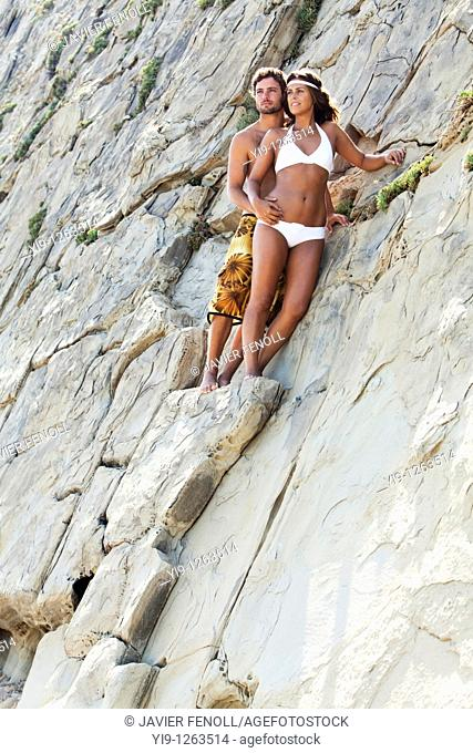 Portrait of a cute young couple relaxing on the rocks