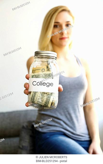 Caucasian woman showing jar of money for college