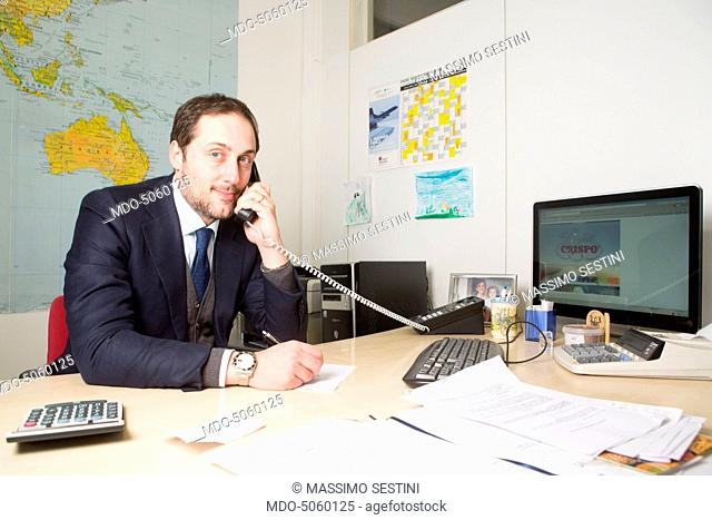 The entrepreneur Gianfranco Crispo speaking over the phone in his office. Gianfranco Crispo is the commercial manager of the confectionery company Crispo -...
