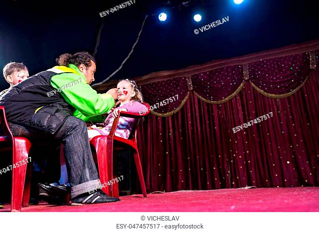 Man Applying Clown Make Up to Face of Girl Sitting in Red Plastic Chair on Empty Stage with Boy Looking On