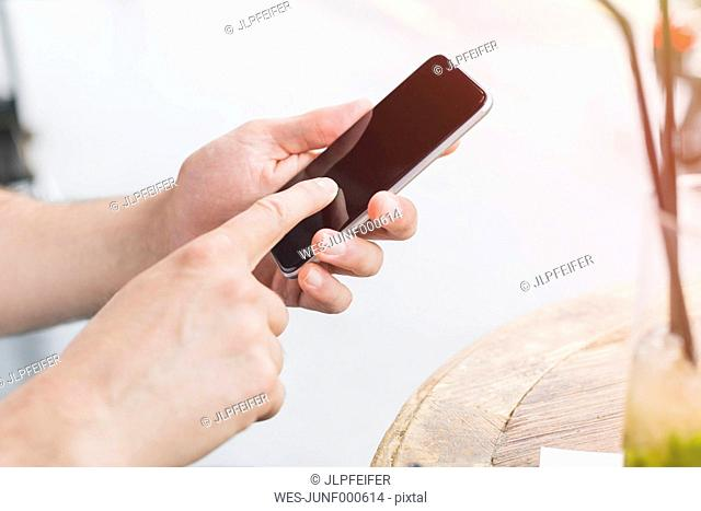 Man's index finger typing on display of his smartphone