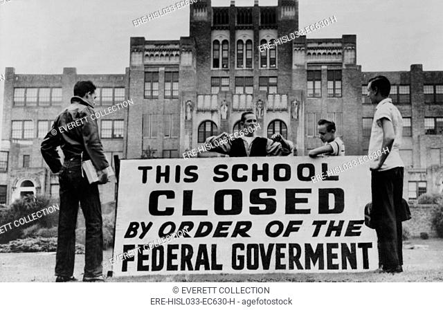 Little Rock Central High was closed to avoid integration. Four students pose with a large sign reading 'This school closed by order of the federal government
