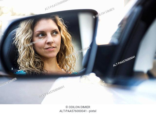 Young woman driving car, reflection in side-view mirror