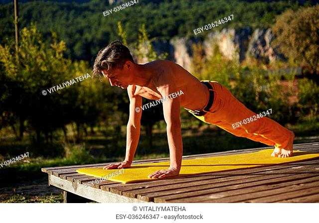 young man doing yoga in the early morning on the garden terrace of the house