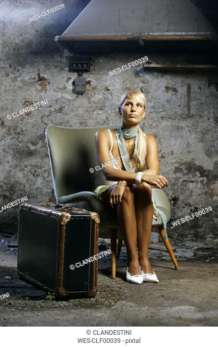 Young woman sitting on armchair, looking up
