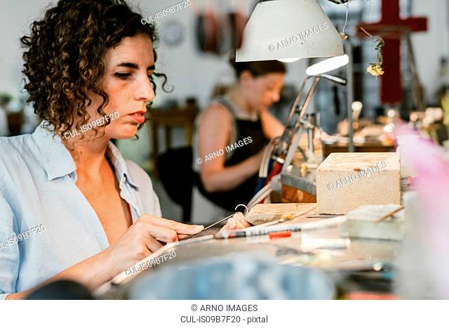 Female jeweller shaping silver metal at workbench