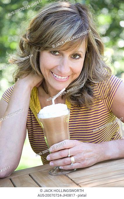 Portrait of a mature woman holding a glass of chocolate milkshake
