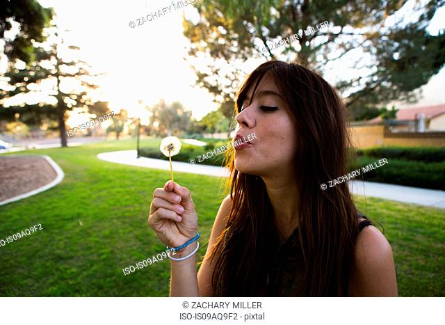 Young woman blowing dandelion clock in park