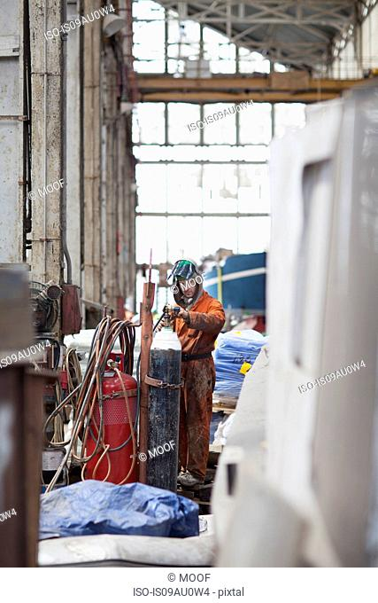 Welder checking gas cylinder in shipyard workshop