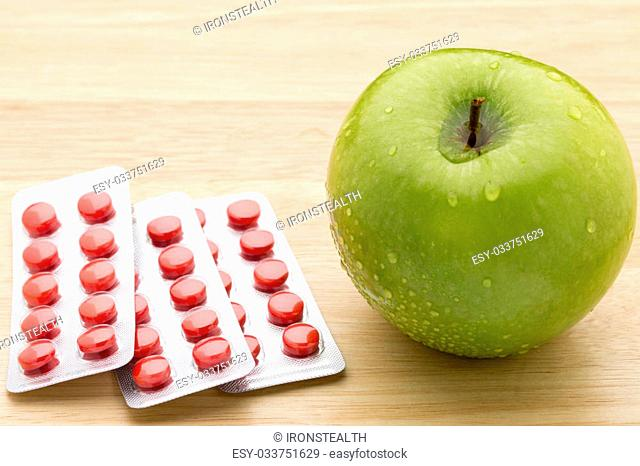 Red pills blister pack and green apple on wooden background