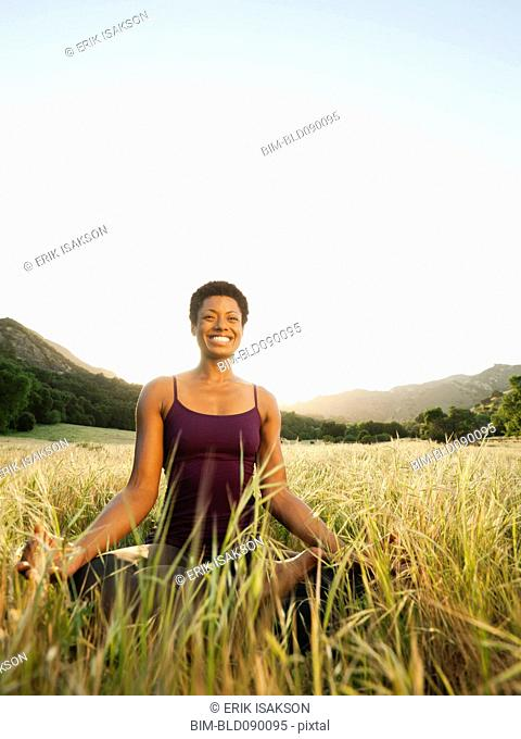 Mixed race woman practicing yoga in remote field