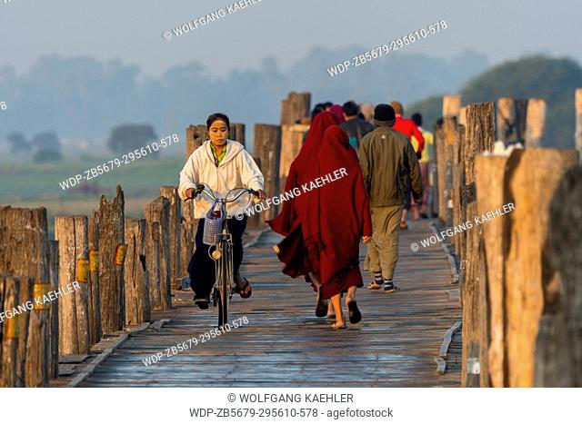 People on U Bein Bridge (built around 1850 and is believed to be the oldest and longest teakwood bridge in the world) spanning Taungthaman Lake near Amarapura