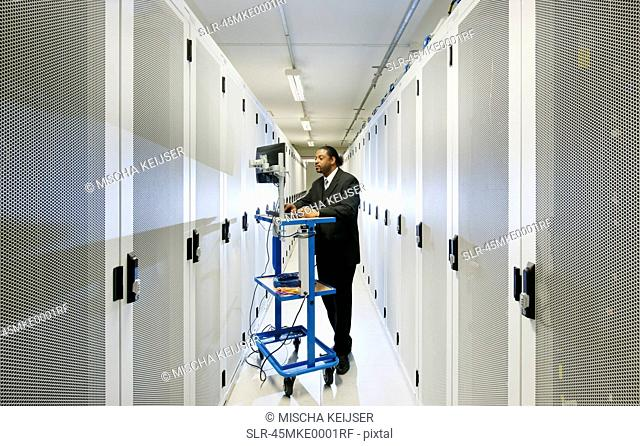 Businessman using computer with servers