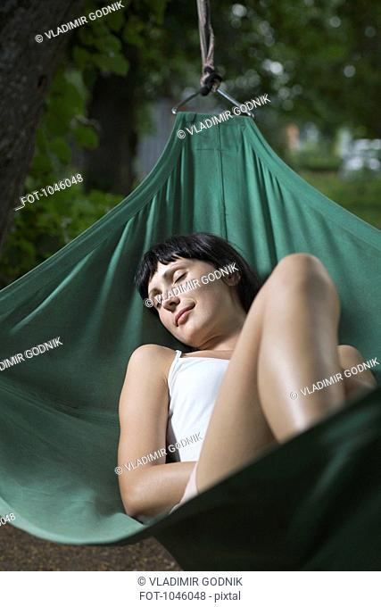 A woman lying in a hammock, eyes closed