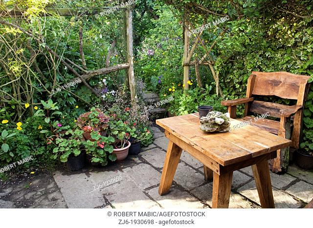 Secluded relaxing area with wooden garden furniture surrounded with potted arrangements and cottage style planting, Kent England