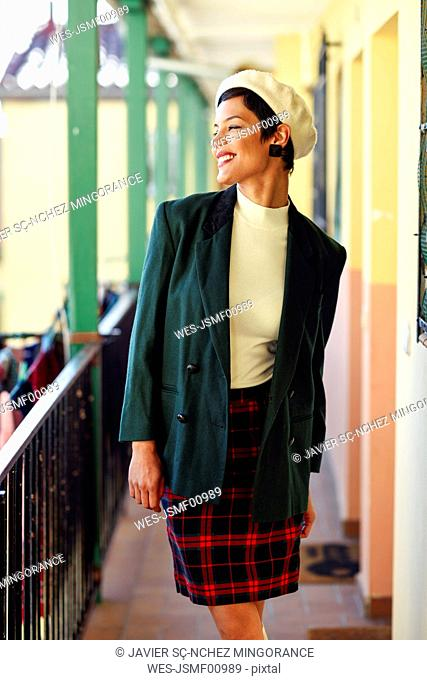 Smiling fashionable young woman walking on porch of an apartment building