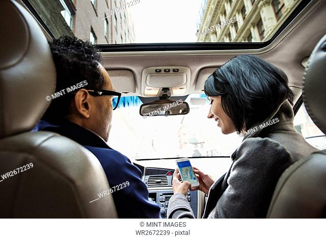 A young woman and young man in a car looking at a map on the display of a cellphone, seen from the back seat