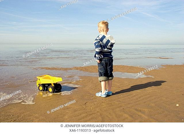 A young blond boy stands next to his yellow toy dump truck on a beach at the edge of the water as the tide comes in, looking out to sea
