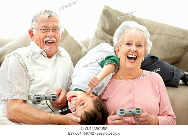 Portrait of happy Grandparents and small boy having fun playing video games at home