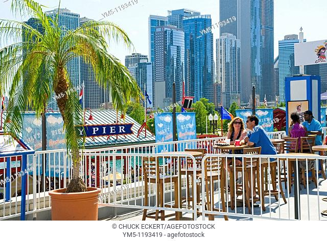 Couples sitting at sidewalk cafe atop Navy Pier with Chicago skyline