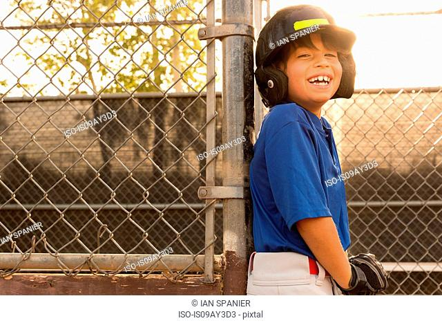 Laughing boy leaning against fence at baseball practise