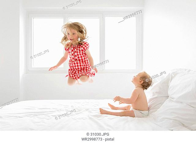 Smiling blond girl wearing red and white checkered dress jumping on bed, baby boy sitting next to her, watching