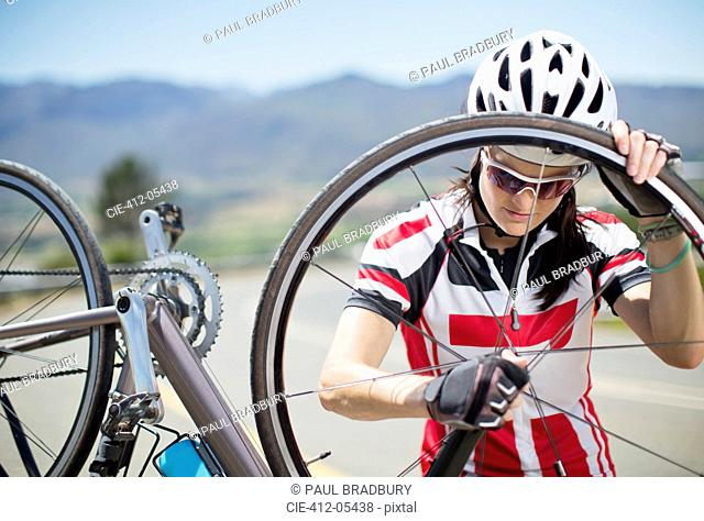 Cyclist adjusting tire on rural road