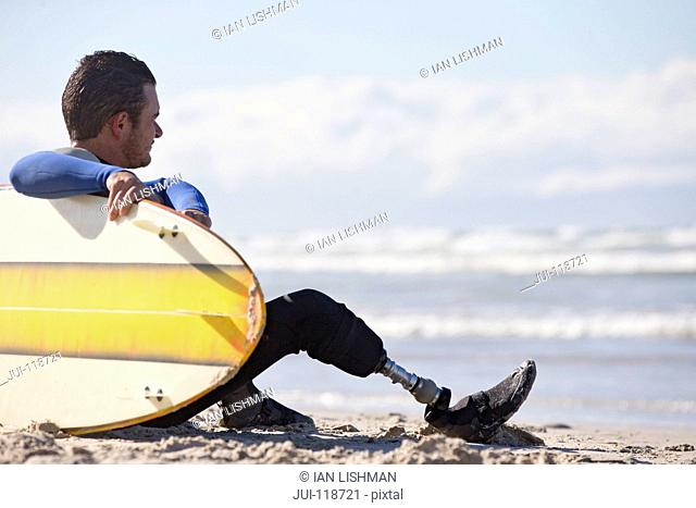 Surfer With Artificial Leg Sitting On Beach