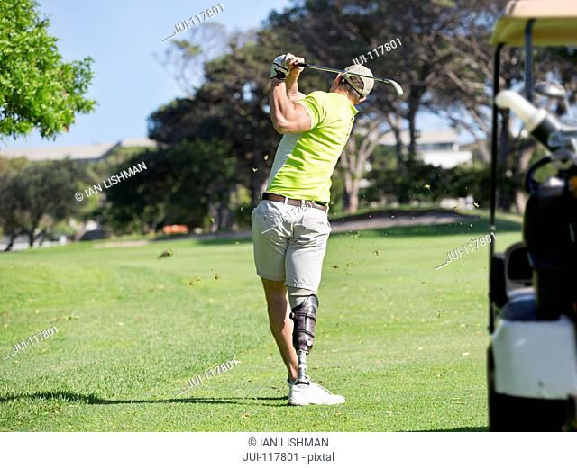 Rear View Of Golfer With Artificial Leg Hitting Ball On Fairway