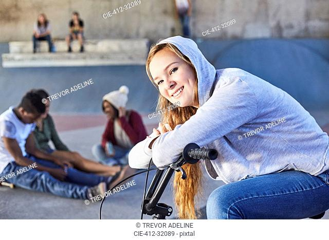 Portrait smiling teenage girl leaning on BMX bicycle at skate park
