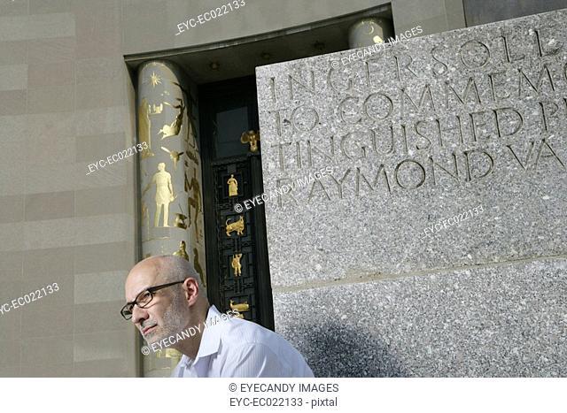 mature man with glasses looking away, against memorial