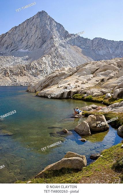 USA, California, Sequoia National Park, Five Lakes trail, Hiker sitting at edge of lake