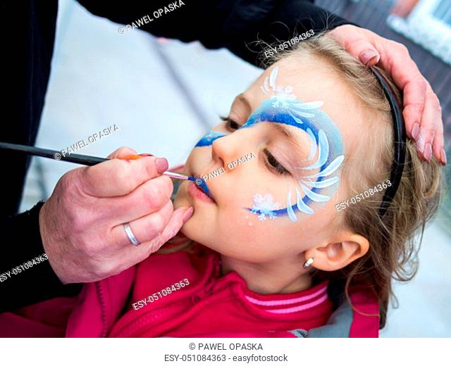 Little girl having her face painted during party by an artist