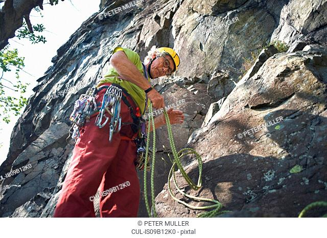 Low angle view of rock climber preparing climbing rope