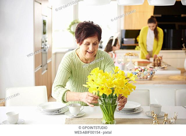 Senior woman arranging flowers on dining table with family in background