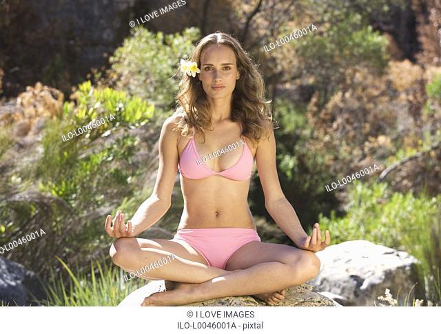 Young woman in a bikini practicing yoga