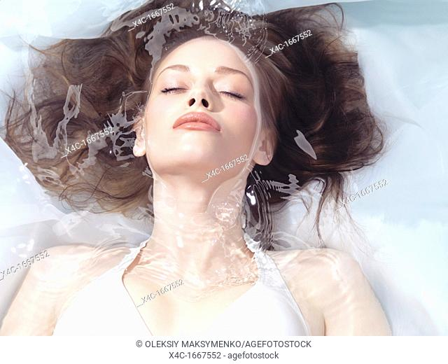 Natural look beauty portrait of a young woman lying relaxed in water with closed eyes  Beauty treatment concept