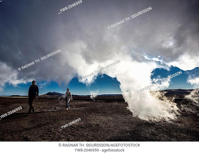 Couple walking under Geothermal Steam, Namaskard- Geothermal Volcanic area, Northern Iceland