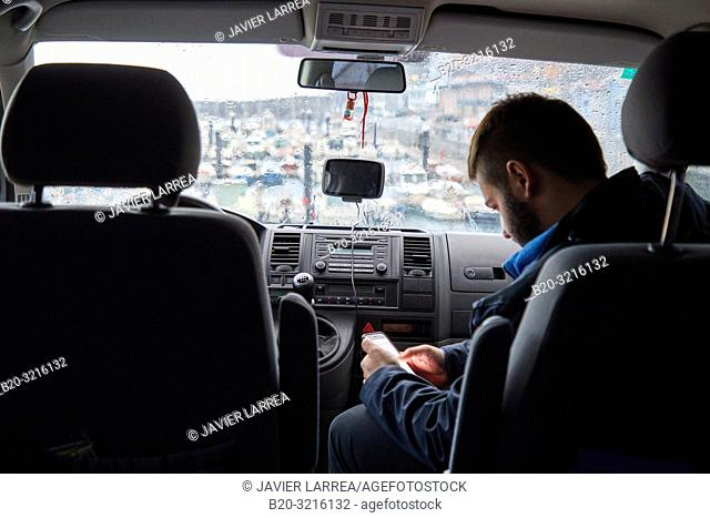 Young man looking at a smartphone inside a car, Rain, Port, Mutriku, Gipuzkoa, Basque Country, Spain, Europe