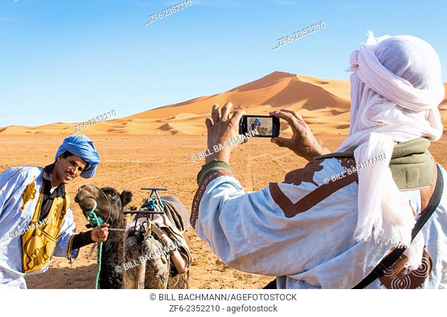Morocco Sahara Desert sand dunes in Las Palmeras area with local man taking cell phone phoyo of his friend and camel and peaks and sand