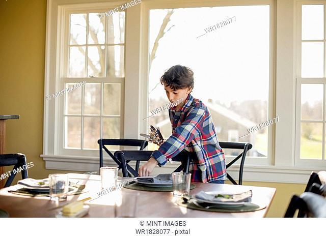 A young boy setting the table with cutlery and glasses