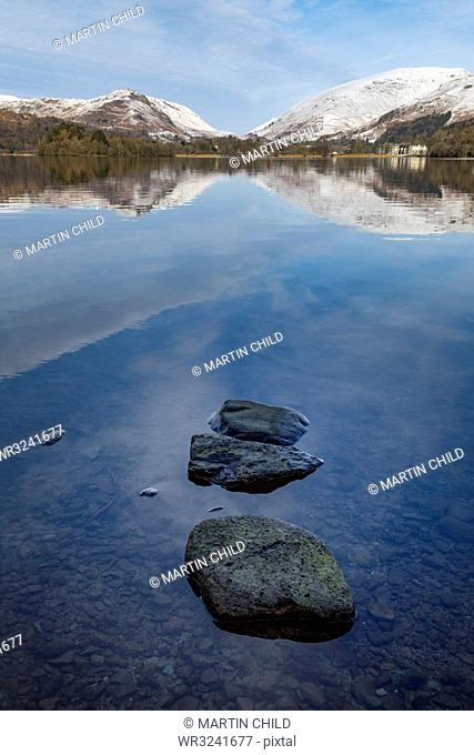 Stones in shallow water and perfect reflection of snow covered mountains and sky in the still waters of Grasmere, Lake District National Park